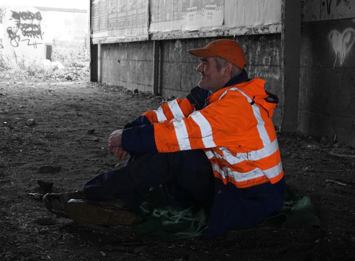 Auf dem Bild siehst du einen Obdachlosen unter einer Brücke.